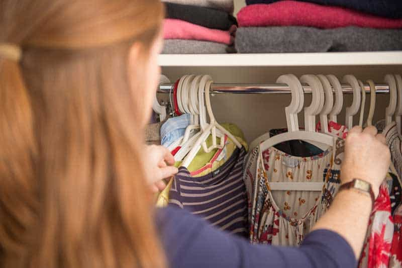 swishing-woman-searching-clothes-on-hangers