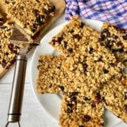Soft Chewy Flapjacks with dried fruit cut up on plate and chopping board