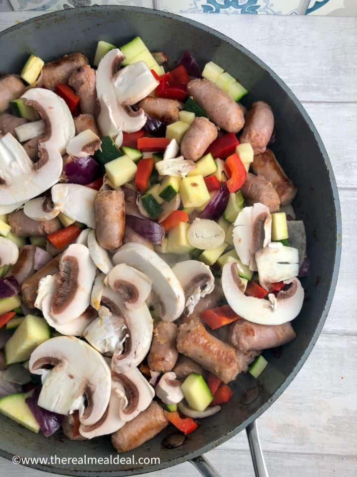 sausages red onion pepper courgette mushroom frying in pan