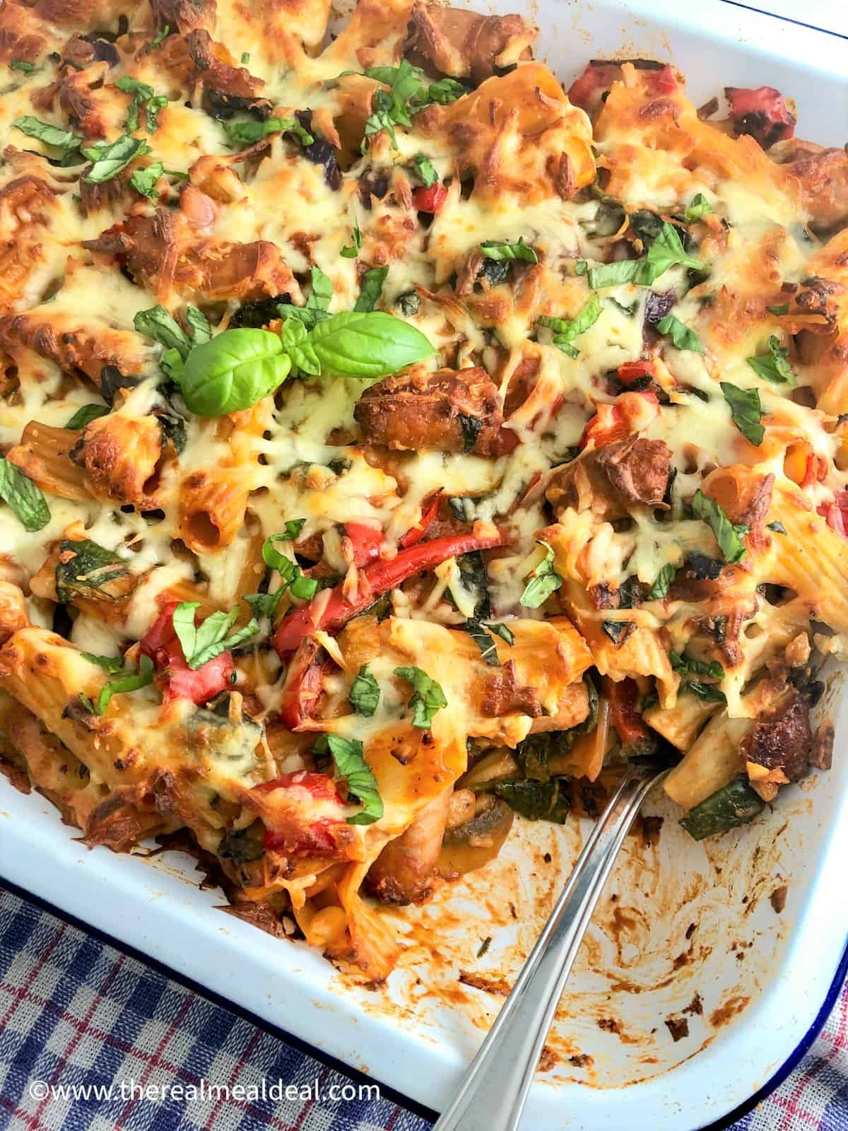 sausage pasta bake in tray 1 portion removed