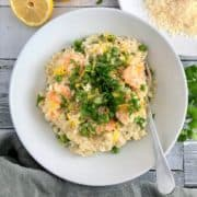 prawn and pea risotto in bowl topped with lemon zest and fresh parsley