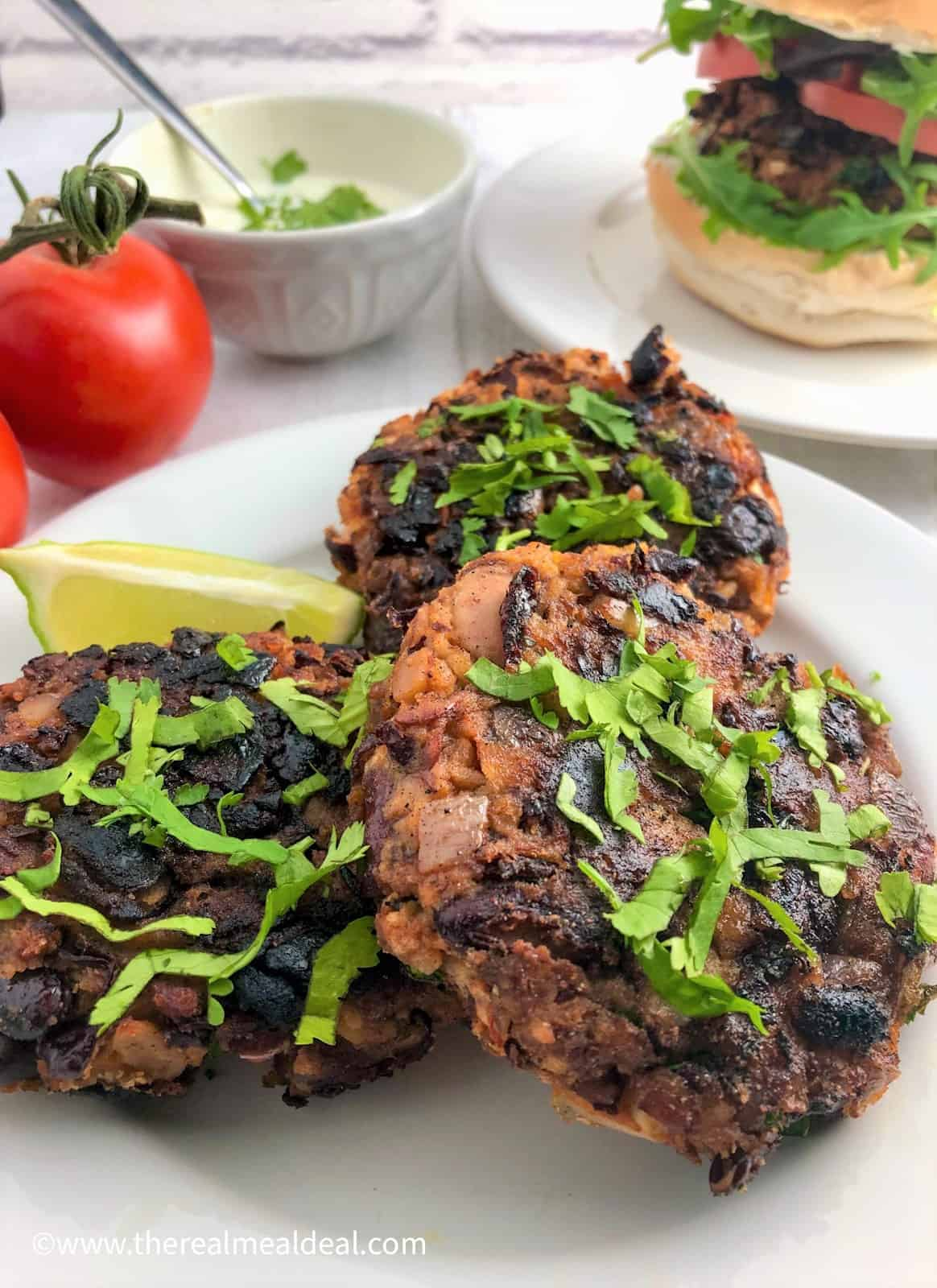 3 spicy bean burgers on plate topped with fresh coriander leaves bean burger in bun in background with tomatoes and yoghurt dip