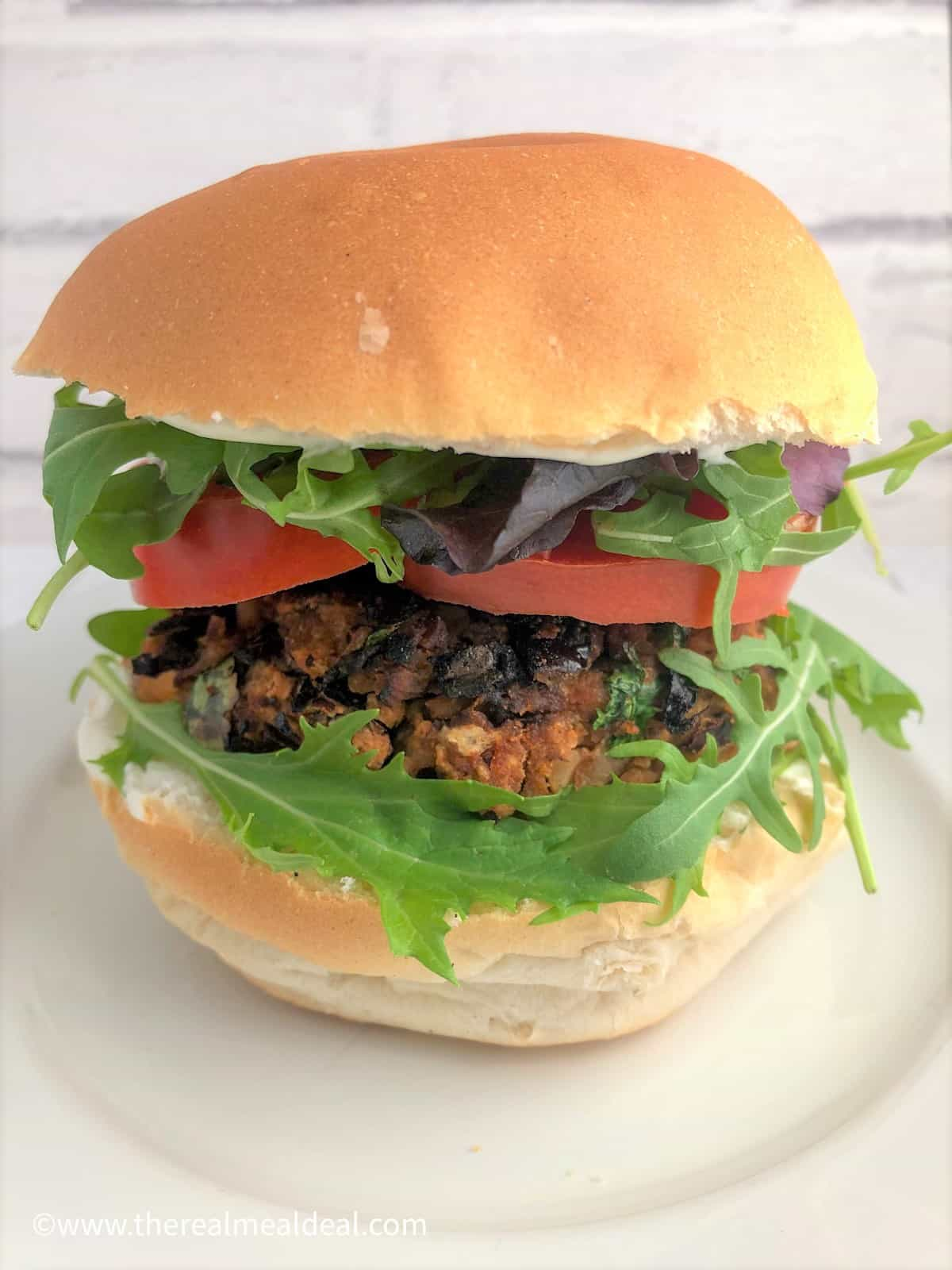 spicy bean burger in bun with rocket sliced tomato