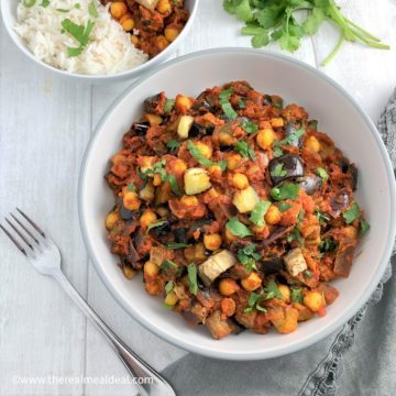 aubergine chickpeas in tomato curry sauce in bowl topped with fresh corainder leaves