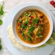 creamy fish curry with coconut milk topped with fresh corainder leaves and served with white rice and lime wedges
